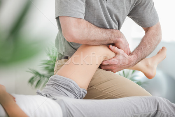 Man manipulating the leg of a woman while she is lying in a room Stock photo © wavebreak_media