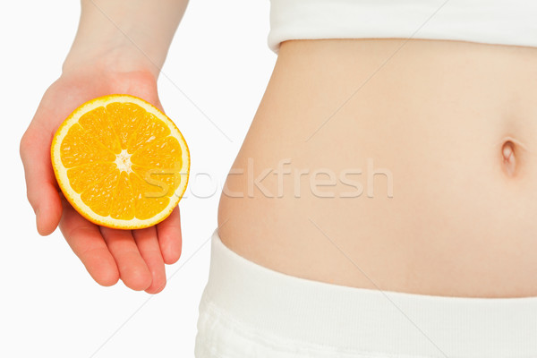 Woman placing an orange near her belly against white background Stock photo © wavebreak_media