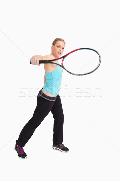 Woman playing tennis with a racket against white background Stock photo © wavebreak_media