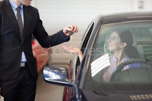 Smiling woman in a car taking keys in a car dealership Stock photo © wavebreak_media