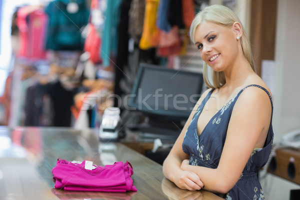 Woman standing behind the counter smiling with clothes folded on the counter Stock photo © wavebreak_media