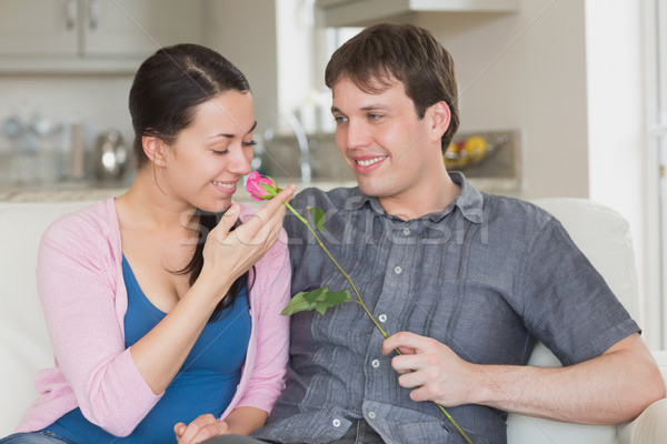 Man presenting flower to girlfriend in living room Stock photo © wavebreak_media