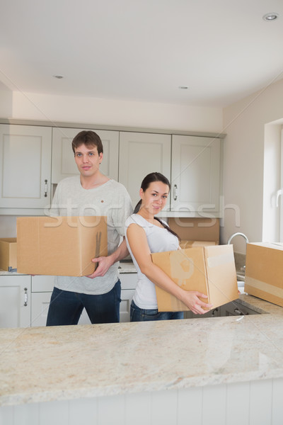 Two young people standing in the kitchen while holding boxes for a relocation Stock photo © wavebreak_media