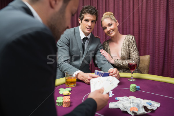 Couple playing poker and smiling in casino Stock photo © wavebreak_media