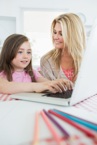 Little girl typing on laptop with mother smiling in the kitchen Stock photo © wavebreak_media