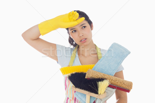 Weary woman holding brushes and mops and wiping her brow Stock photo © wavebreak_media