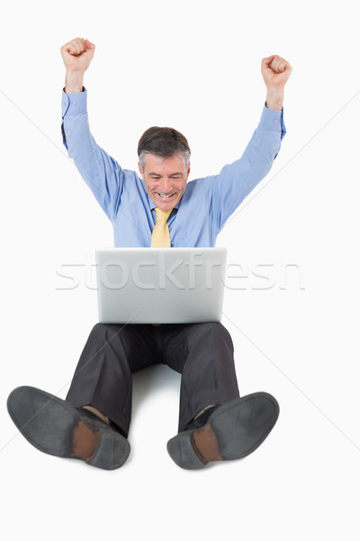Succesful man on the floor with his laptop with arms in the air Stock photo © wavebreak_media