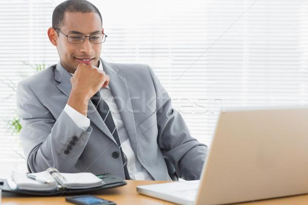 Empresário sessão laptop mesa de escritório sorridente jovem Foto stock © wavebreak_media