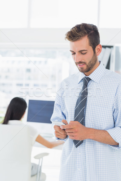 Male artist text messaging with colleague in background Stock photo © wavebreak_media