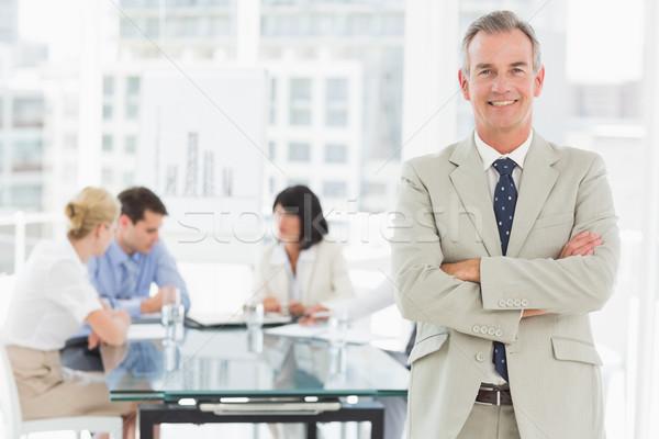 счастливым бизнесмен глядя камеры сотрудников обсуждать Сток-фото © wavebreak_media