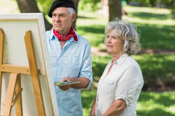 Woman watching mature man paint in park Stock photo © wavebreak_media