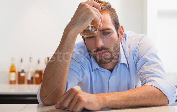 Drunk businessman clutching whiskey glass to head Stock photo © wavebreak_media