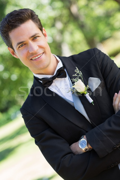 Confident bridegroom with arms crossed in garden Stock photo © wavebreak_media