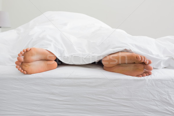 Couples feet sticking out from under duvet Stock photo © wavebreak_media