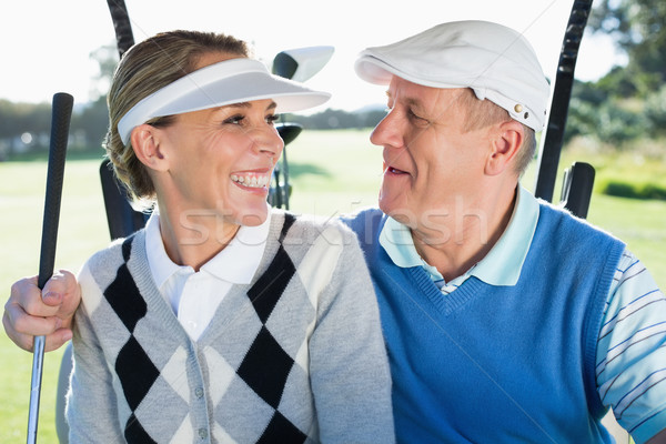Happy golfing couple sitting in golf buggy smiling at each other Stock photo © wavebreak_media