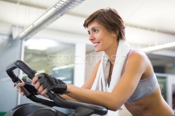 Uygun gülümseyen kadın egzersiz bisiklet spor salonu Stok fotoğraf © wavebreak_media
