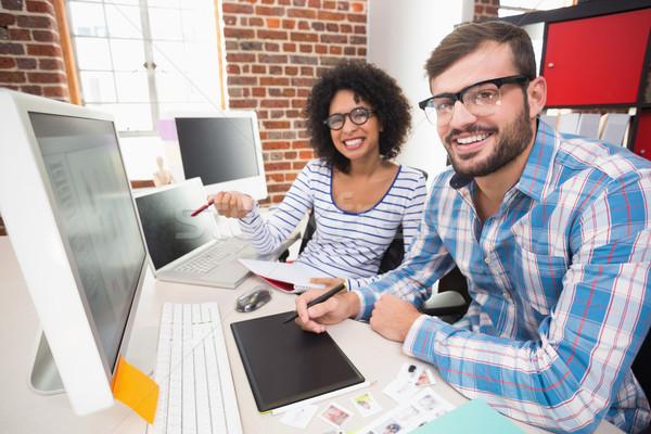 Smiling photo editors using digitizer in office Stock photo © wavebreak_media