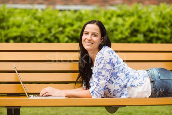 Przypadkowy brunetka ławce wpisując laptop parku Zdjęcia stock © wavebreak_media