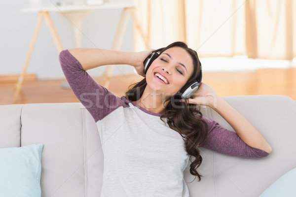 Pretty brunette listening to music on the couch Stock photo © wavebreak_media