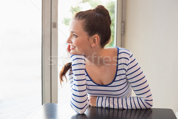 Stock photo: Pretty brunette smiling at the table