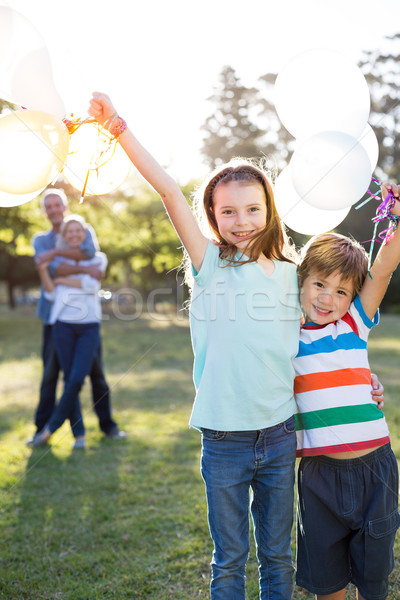 Happy siblings holding balloons at the park  Stock photo © wavebreak_media