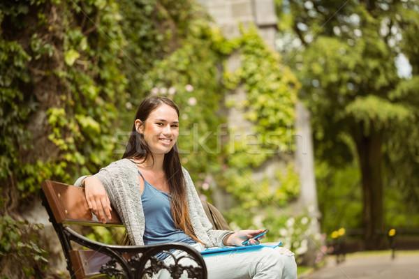 Smiling student sitting on bench holding her mobile phone  Stock photo © wavebreak_media