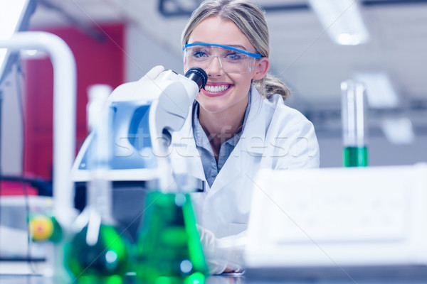 Happy science student working with microscope in the lab Stock photo © wavebreak_media