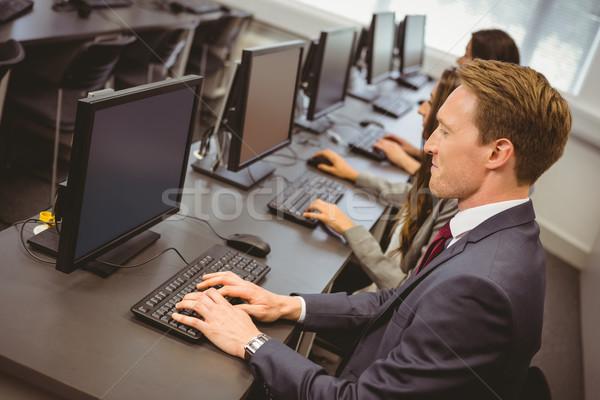 Three focused people working in computer room Stock photo © wavebreak_media