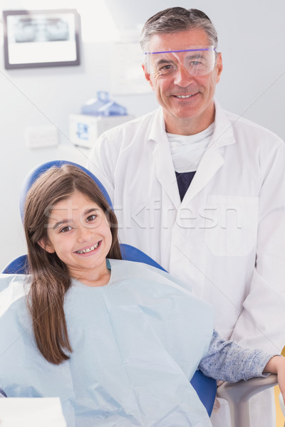Smiling dentist with safety glasses and happy young patient Stock photo © wavebreak_media