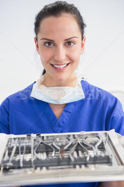 Smiling dentist holding tray with equipment  Stock photo © wavebreak_media