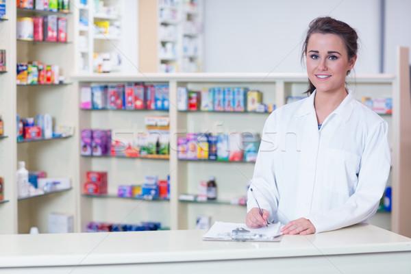 Smiling trainee in lab coat writing a prescription Stock photo © wavebreak_media