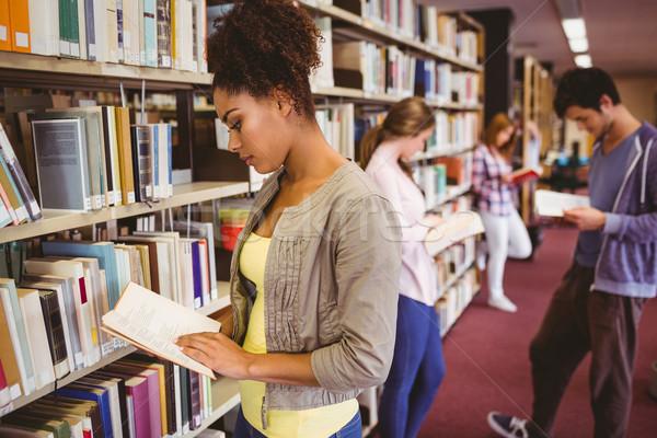 Diákok olvas könyv könyvespolcok könyvtár iskola Stock fotó © wavebreak_media