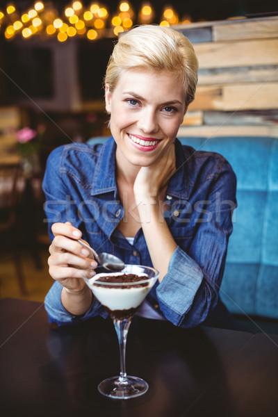 Smiling blonde eating a creamy chocolate  Stock photo © wavebreak_media