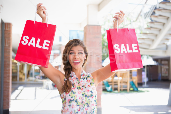 Portrait of euphoric woman holding two sale shopping bags Stock photo © wavebreak_media