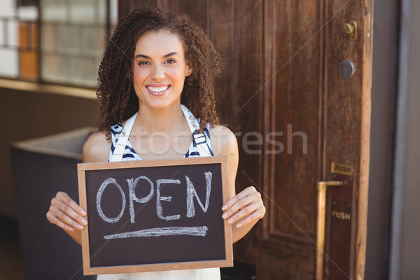 Stock photo: Smiling waitress showing chalkboard with open sign
