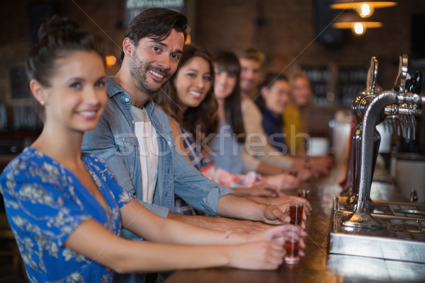 Happy friends holding short glasses on counter in bar Stock photo © wavebreak_media