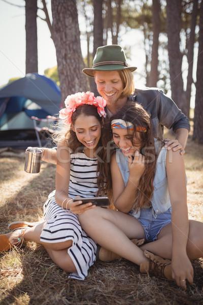 Boldog barátok okostelefon ül mező erdő Stock fotó © wavebreak_media