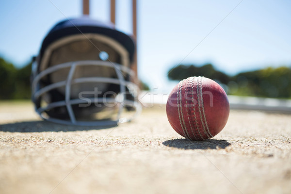 Close up of cricket ball with helmet on pitch Stock photo © wavebreak_media