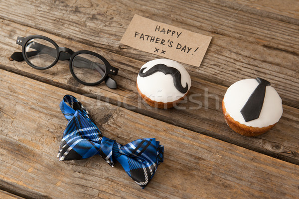Happy fathers day text by decorated cupcakes and eyeglasses on table Stock photo © wavebreak_media