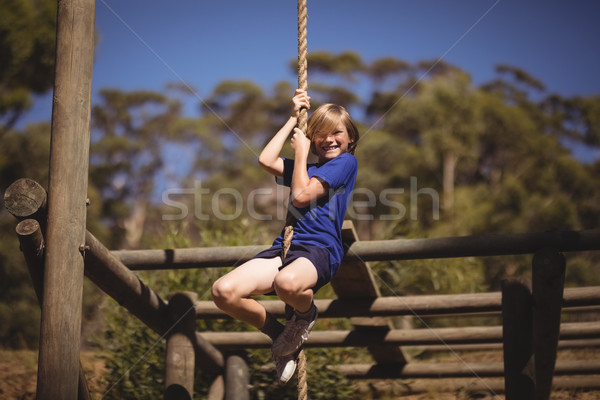 Portrait of smiling girl climbing rope during obstacle course Stock photo © wavebreak_media