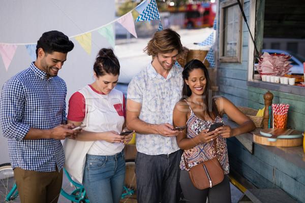 Barátok mobiltelefon pult boldog üzlet nő Stock fotó © wavebreak_media