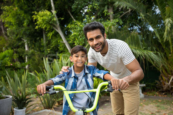 Portrait of father with son sitting on bicycle Stock photo © wavebreak_media