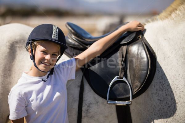 Smiling rider standing with his hand on white horse Stock photo © wavebreak_media