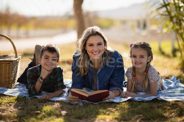 Smiling mother and kids reading novel in park Stock photo © wavebreak_media
