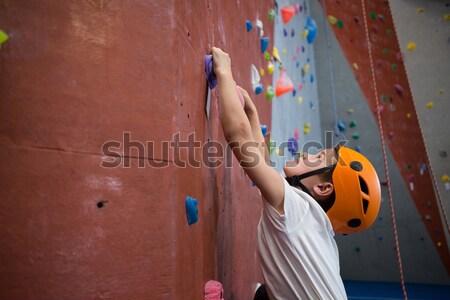 Man wall climbing in gym Stock photo © wavebreak_media