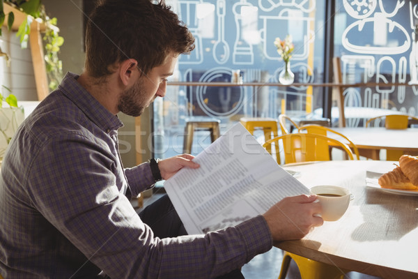 Stock photo: Businessman having coffee while reading newspaper in cafe