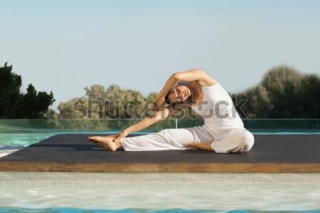 Woman practicing yoga on at poolside Stock photo © wavebreak_media
