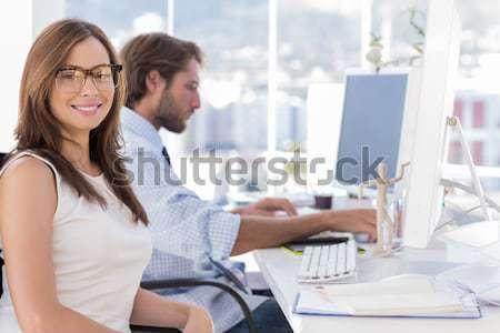 Colegas olhando câmera digital escritório sessão criador Foto stock © wavebreak_media