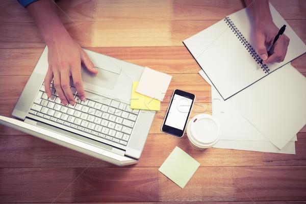 Businessman writing on spiral book using laptop Stock photo © wavebreak_media