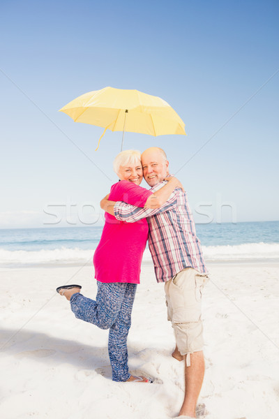 Senior couple embracing and holding umbrella Stock photo © wavebreak_media